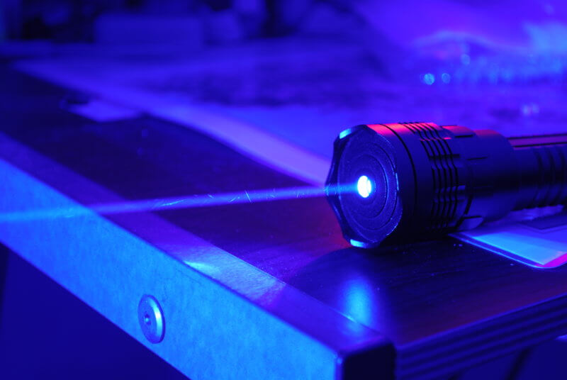 Laser pointer shoots a beam of blue light